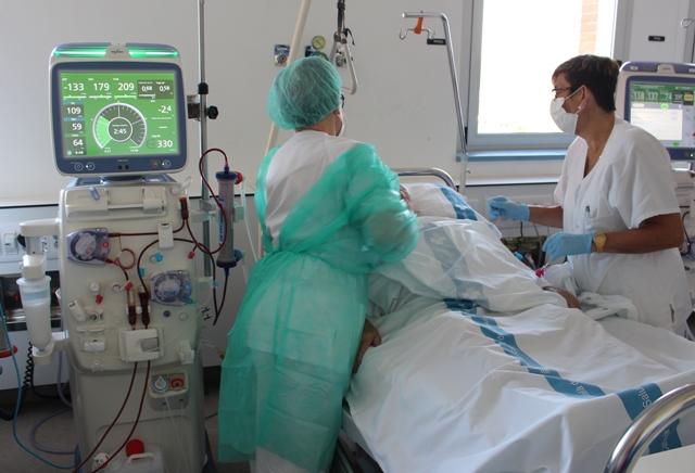 Dues professionals de la Unitat d'Hemodiàlisi atenen un pacient durant una sessió de diàlisi