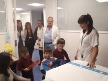 Foto de nens amb les 2 tauletes tàctils que aniran destinades a la UCIP.